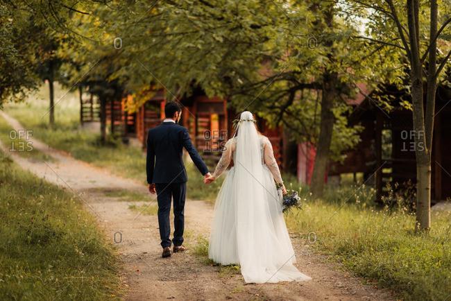 Bridal couple walking along dirt road