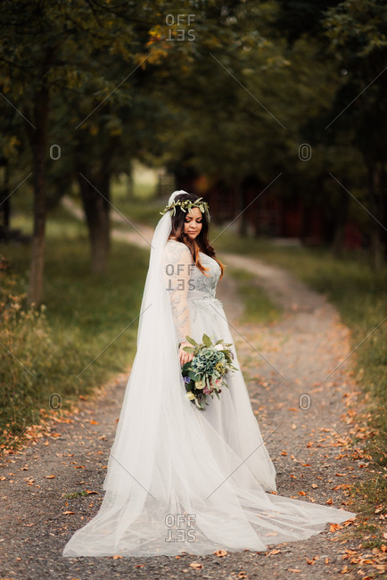 Bride on rural path with bouquet