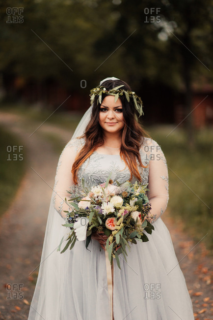 Bride with her bouquet on rural path