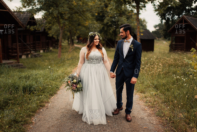Bride and groom walking by cabins
