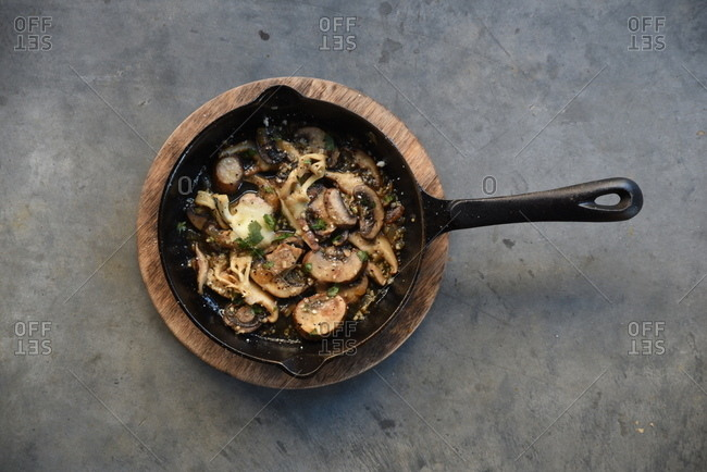 Mushrooms sauteed in skillet with cheese