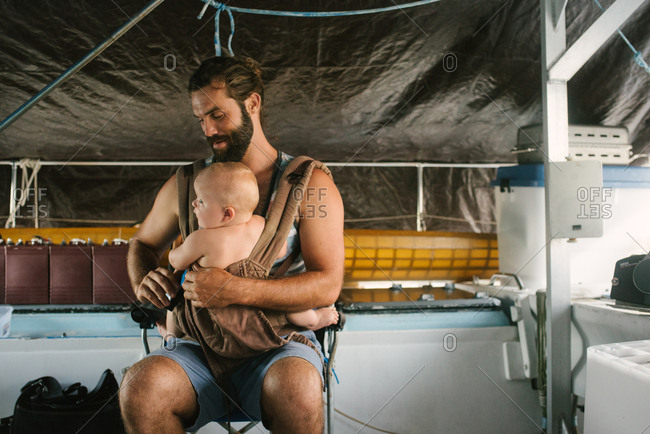 Father strapping baby into a baby carrier