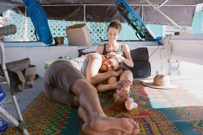 Couple relaxing on a colorful rug on a boat