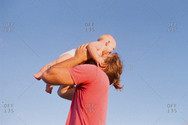 Father lifting baby in the air