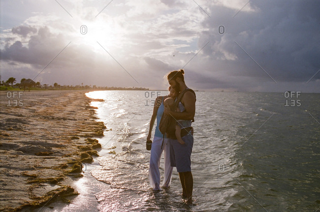 Couple standing in the ocean waves with baby in a carrier