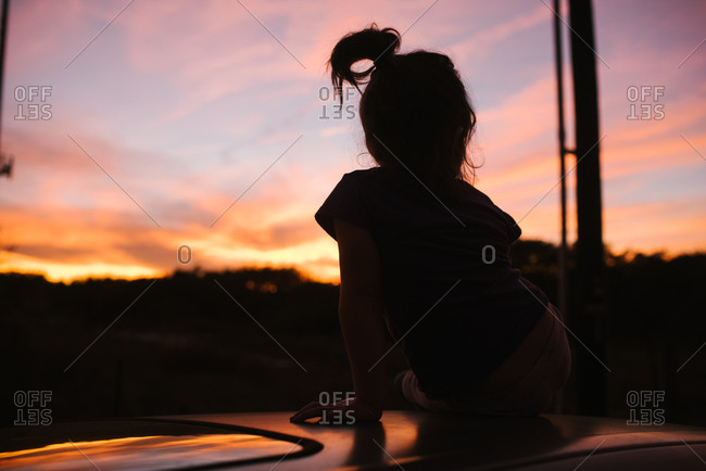 Silhouette of girl with ponytail watching the sunset