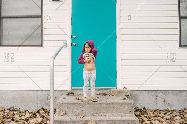Girl standing by blue door lifting her shirt to show her belly