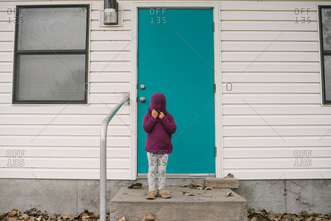 Girl standing by blue door covering her face with the hood of her sweater