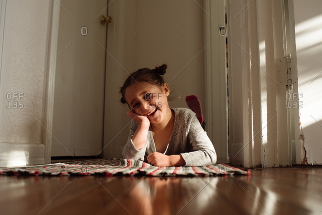 Little girl lying on rug smiling