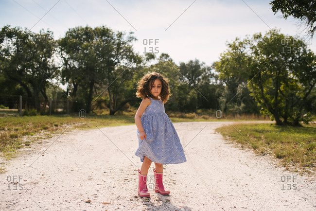 Little girl with curly brown twirling her blue dress