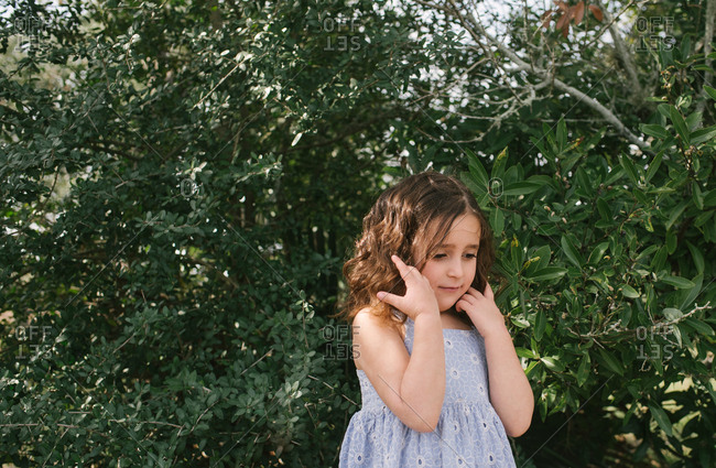 Little girl with curly brown hair standing by a bush