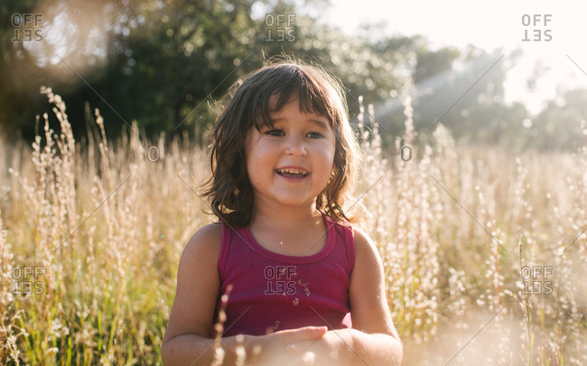 Little girl with standing in a sunny field