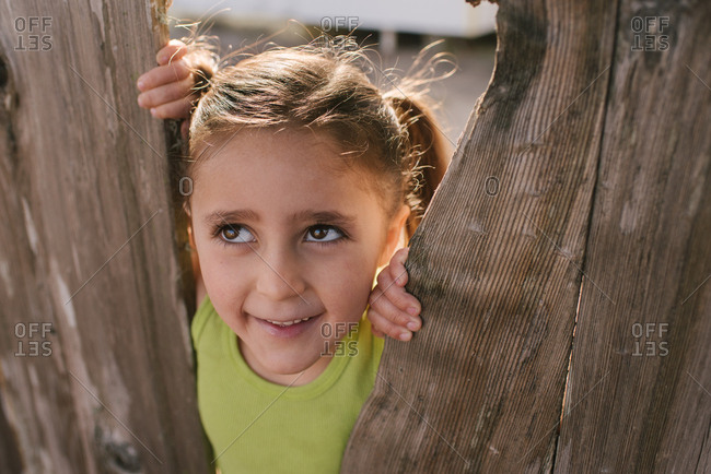 Close up of a little girl standing between wooden boards