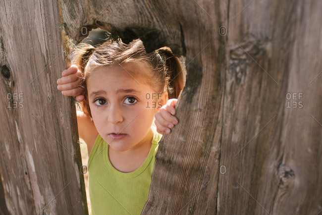 Little girl looking through a hole in a fence