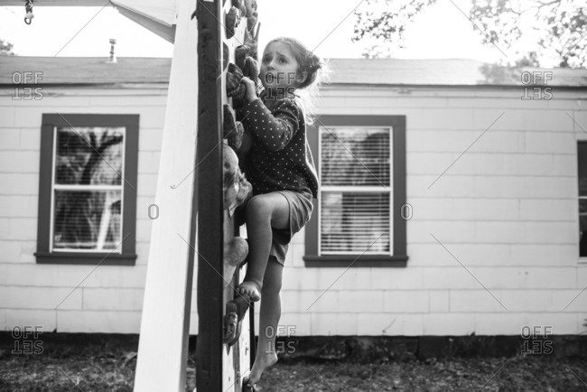 Little girl climbing a rock wall in black and white