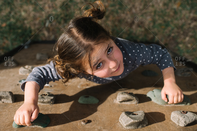 High angle view of a little girl climbing a rock wall