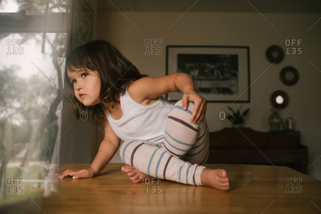 Little girl sitting on table looking out window