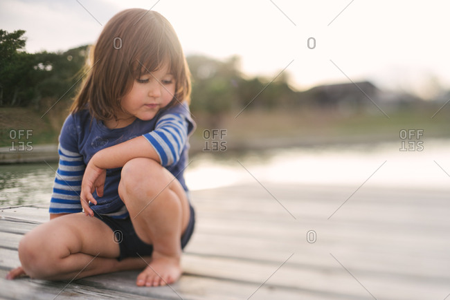 Little girl sitting on a dock looking down