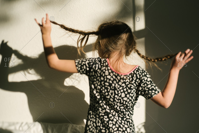 Young girl looking at her shadow while she lifts her braids