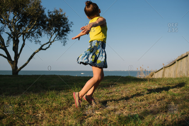 Young girl dancing in a field by the ocean