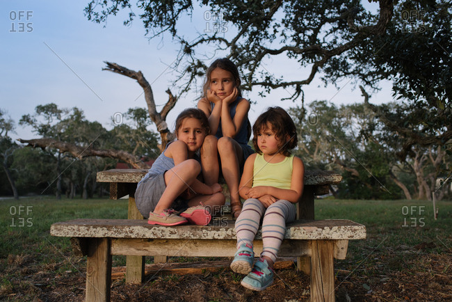 Three young girls sitting on a picnic table
