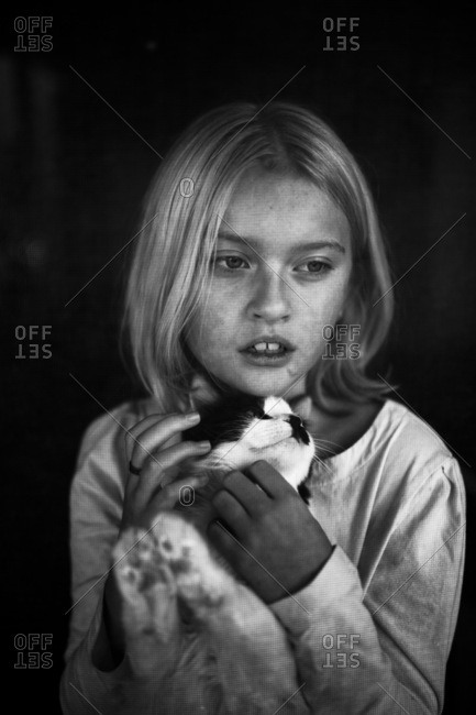 Blonde girl petting a cat in black and white