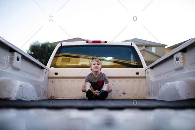 Little blonde boy sitting in the back of a pickup truck