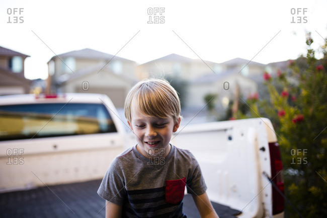 Blonde boy sitting in the back of a pickup truck