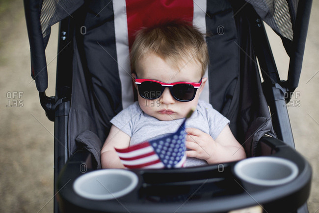 Baby boy with sunglasses in a stroller holding an American flag