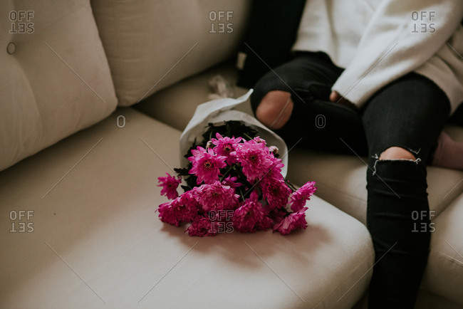 Woman on couch with bouquet of pink flowers
