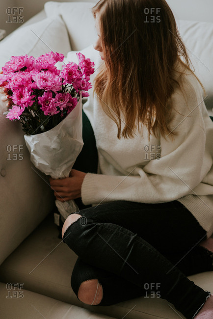 Woman sitting on sofa smelling bouquet of pink flowers