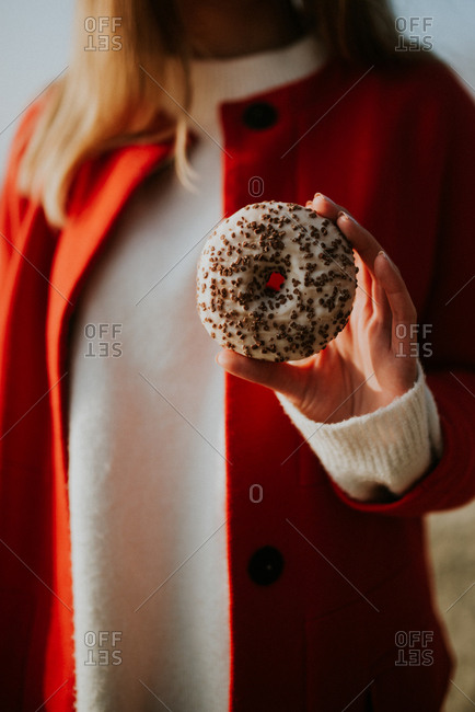 Woman holding donut with chocolate sprinkles