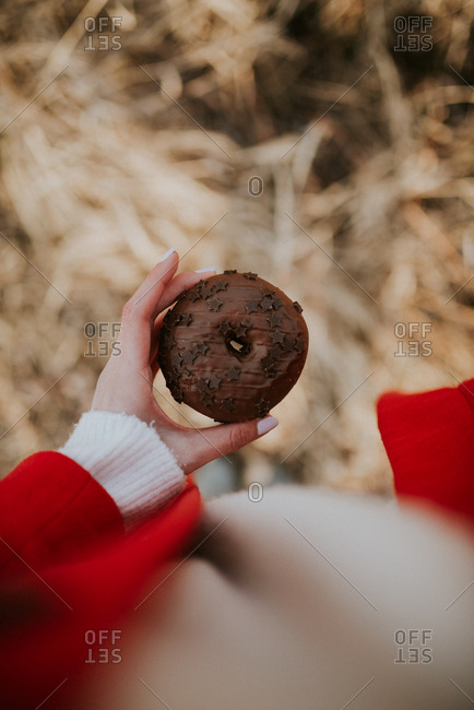 Woman holding chocolate donut with star sprinkles
