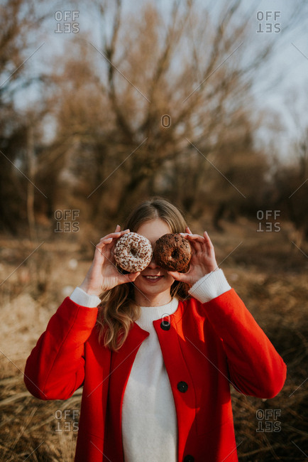 Woman holding two donuts with sprinkles over her eyes