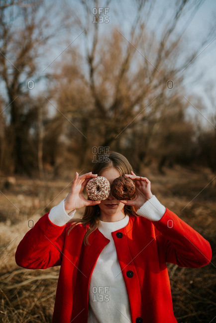 Young woman holding donuts with sprinkles over her eyes