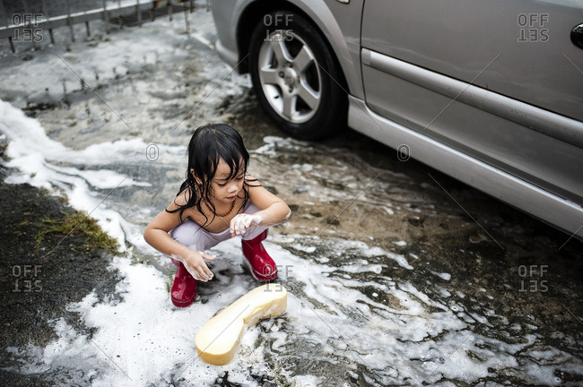 Little boy washing car with soapy sponge