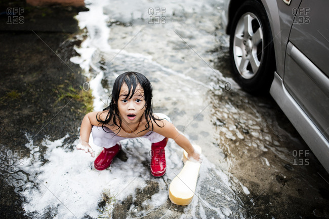 Surprised little boy washing car with soapy sponge