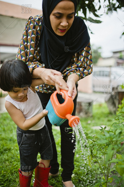 Mother and son watering plants in their backyard