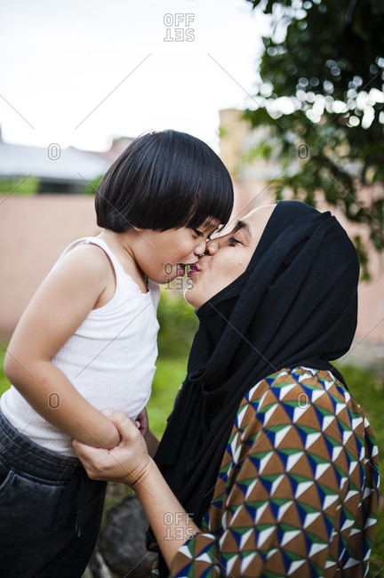 Mother kissing her son outdoors