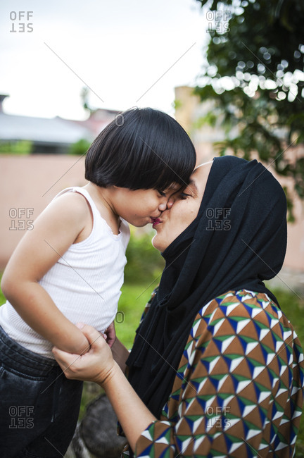 Mother giving her son a kiss outdoors