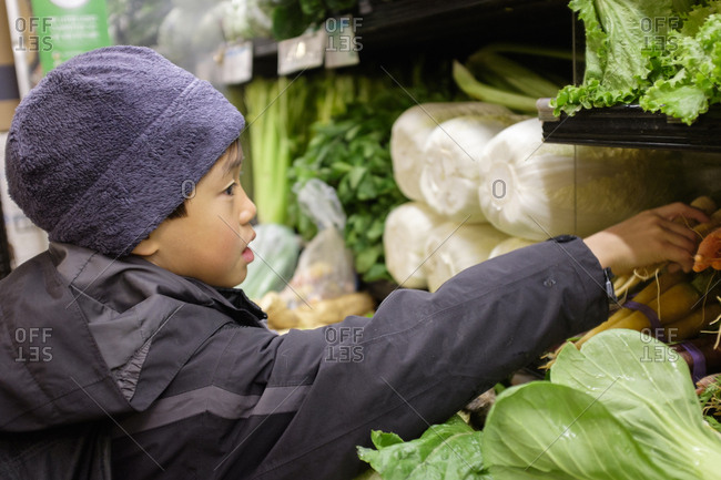 Young boy shopping for vegetables at a grocery store