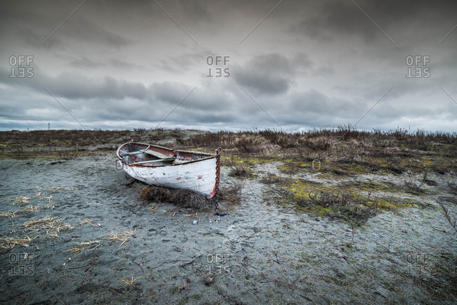 Small weathered boat on dry ground near Puget Sound