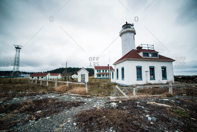 Lighthouse and other buildings on rocky beach on Puget Sound