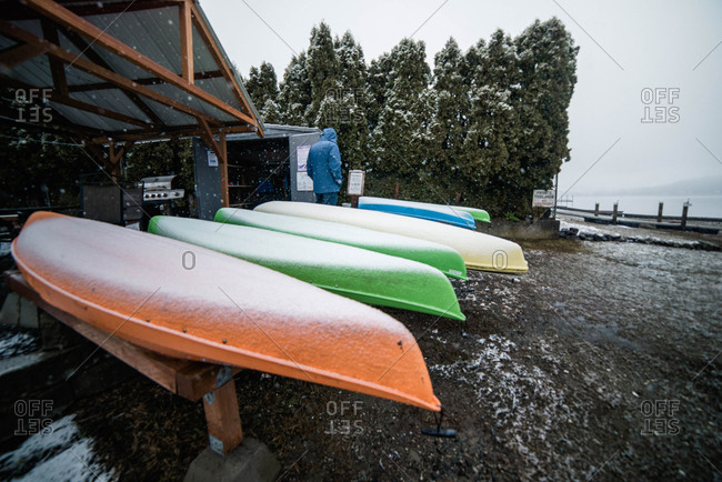 Kayaks with a light dusting of snow stored for the winter along Puget Sound
