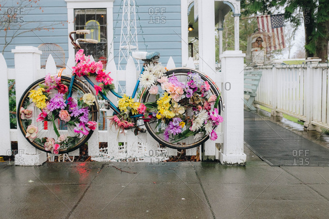 Bicycle decorated with flowers hanging on white picket fence outside home in a small town in Washington