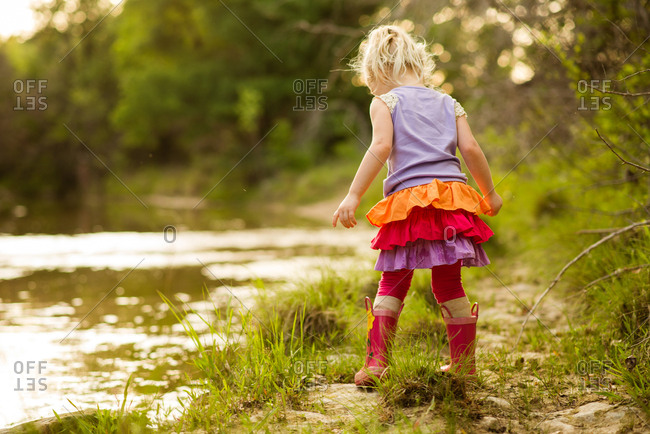 Girl at edge of water in countryside