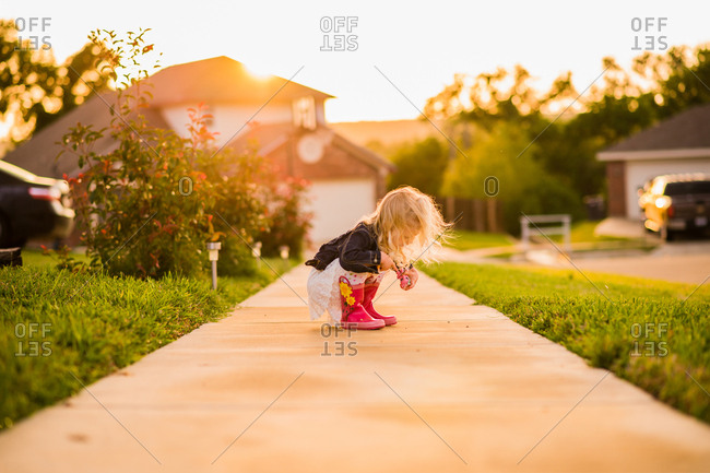 Girl watching insects on sidewalk