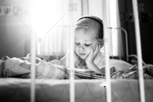 Girl concentrating on tablet in bed