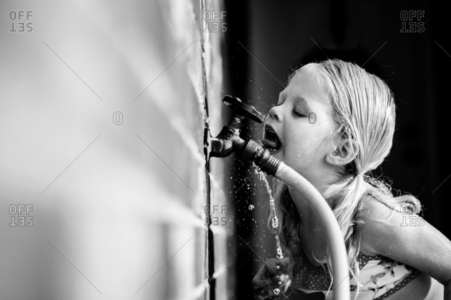 Girl drinking from hose faucet