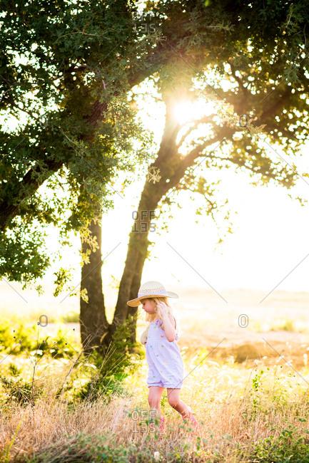 Girl walking through sun dappled meadow